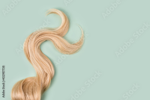 Fotografia Curly blonde hair on mint background