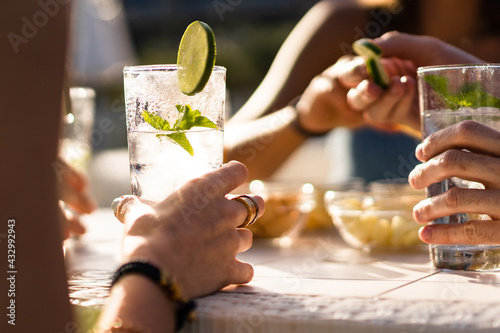 Valokuva Hands holding a fresh alcoholic long drink cocktail on a table