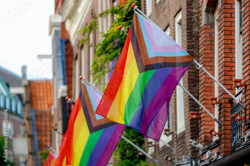 Fotografia Progress pride flag (new design of rainbow flag) waving in the air with blue sky, Celebration of gay pride, The symbol of lesbian, gay, bisexual and transgender, LGBTQ community in Netherlands