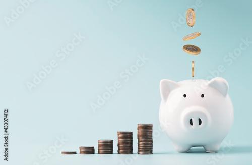 Coins falling to white piggy saving ,  Financial and money deposit concept Fototapeta