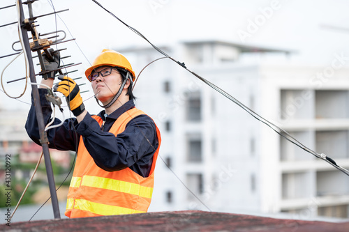 Fotografia Male electrical worker or Asian man electrician wearing safety helmet and reflective suit repairing an old TV antenna and cable on rooftop of building