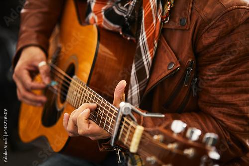 Fotografie, Obraz Young hipster man plays guitar.