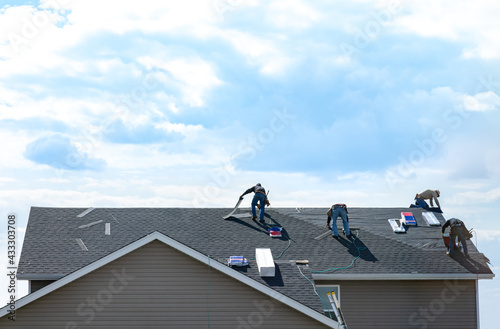 4 construction workers fixing roof against clouds blue sky, install shingles at the top of the house Fototapeta