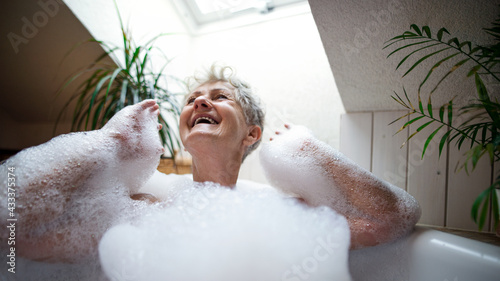 Fotografiet Cheerful senior woman washing in bubble bath tub at home, laughing