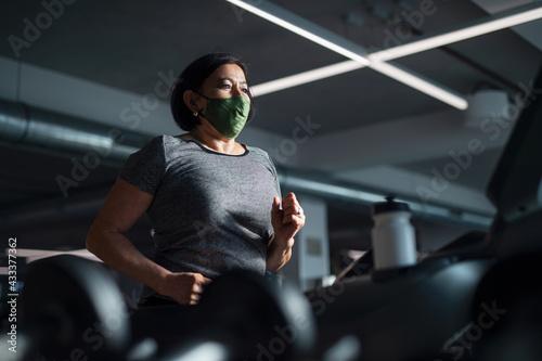 Fototapeta Senior woman with face mask doing exercise on treadmill in gym, coronavirus concept