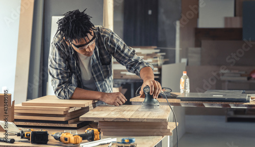 Canvas Print Young black man carpenter working in his workshop.