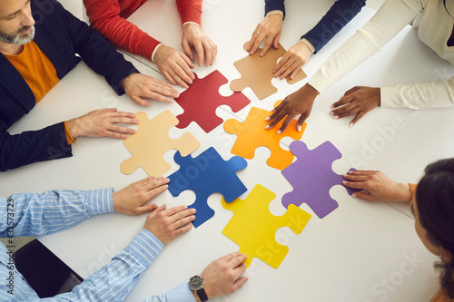 Closeup diverse multinational associates teammate people group moving puzzle pieces on office table for searching and finding solution Fototapeta