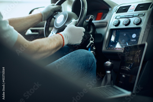 Fotografie, Tablou Close-up of mechanic doing car diagnostic while sitting behind steering wheel at auto repair shop