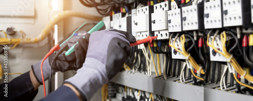 Fotografering Electrician engineer tests electrical installations and wires on relay protection system