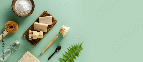 Concept of Eco friendly home cleaning, baking soda, wooden brushes, vinegar, lemon, soap. Top view, flat lay. Copy space.