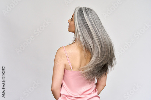 Fotografia Back view of senior mature middle aged older Asian lady with long gray natural coloring vibrant silky hair