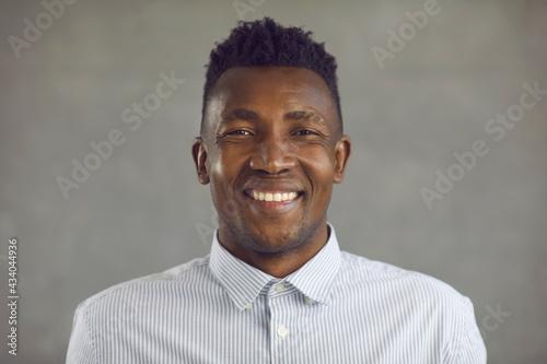 Billede på lærred Studio portrait of happy young black man with stubble on shaved face smiling at camera with sincere positive emotions