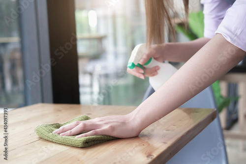 Foto Hand holding microfiber cleaning cloth and spray bottle on work surface concept