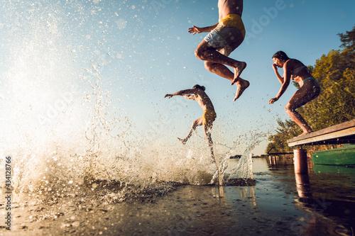 Obraz na plátně Friends having fun enjoying a summer day swimming and jumping at the lake