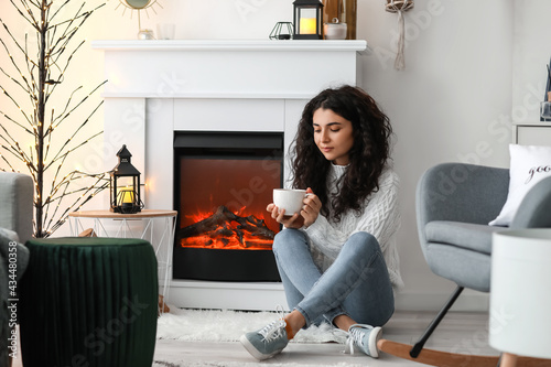 Stampa su Tela Beautiful woman drinking tea near fireplace at home