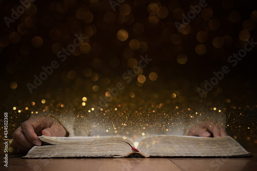 Obraz na plátne A person reading a Holy Bible with gold background.