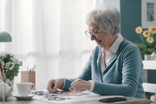 Happy elderly woman solving a puzzle and drinking tea Fotobehang