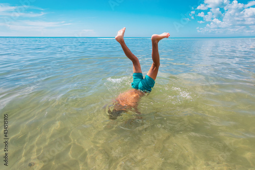 Canvastavla boy diving into water, kid making handstand in sea, vacation fun