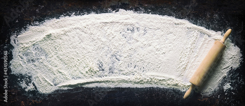 Valokuva Abstract baking background with the rolling pin and flour on dark table