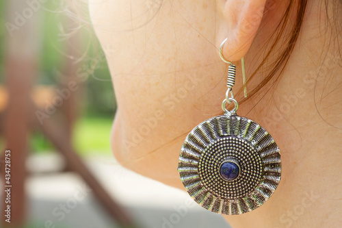 Canvas Outdoor detail of female ear wearing metal ornamental earring