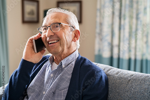 Happy carefree old man talking over phone