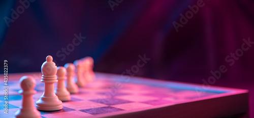 Billede på lærred Chess pieces on a chessboard on a dark background shot in neon pink-blue colors