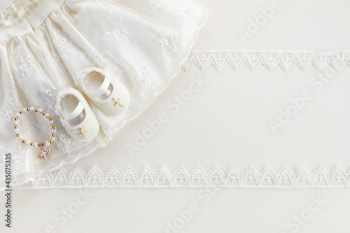 Photographie Christening background with baptism baby dress, shoes, and cross on pastel backg