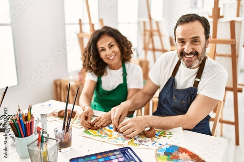 Fotografía Two middle age students smiling happy modeling clay sitting on the table at art school