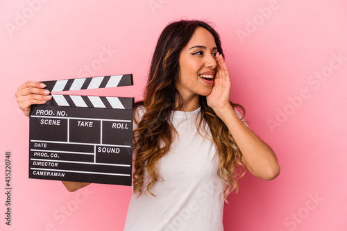 Young mexican woman holding clapperboard isolated on pink background shouting and holding palm near opened mouth Fototapet
