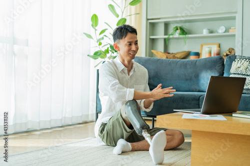 Photo オンライン会議中の義足の男性