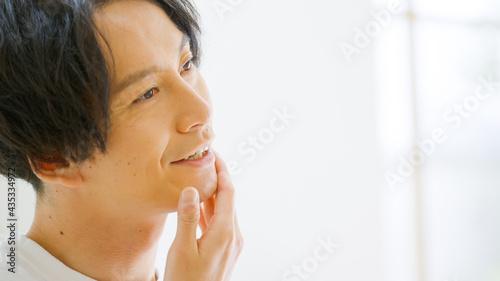 Fotografija 笑顔で顔を触る男性