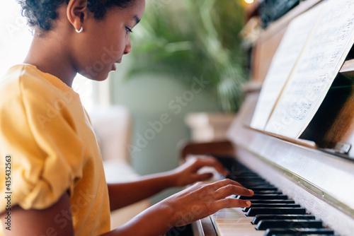 Fototapeta Musical education. Happy black girl playing the piano