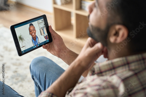 Slika na platnu Young indian latin bearded businessman having videocall meeting at home with black female doctor therapist using tablet computer pointing to throat