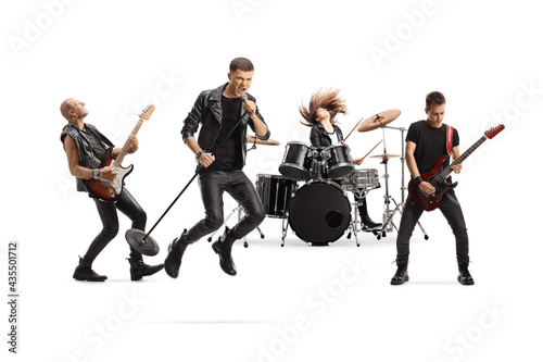Fototapeta Music band with a male singer jumping with a microphone