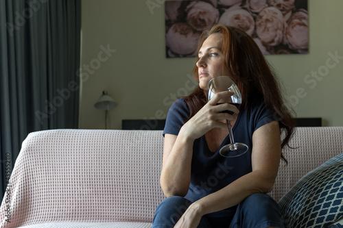 Fotografiet woman sitting on sofa and drinking wine