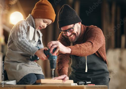 Billede på lærred Father and son drilling wooden detail in workshop