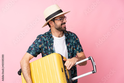Carta da parati Young caucasian man over isolated background in vacation with travel suitcase an
