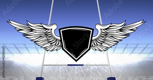Composition of white digital shield with wings over rugby field
