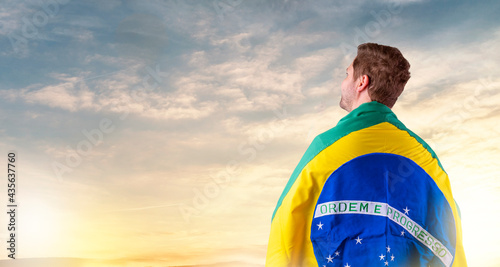 Fotografie, Obraz Brazilian man with Brazilian flag looking at the horizon