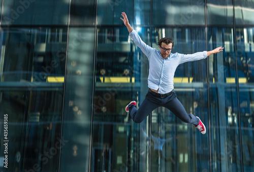 Man in casual wear falling off modern glass building Fototapet