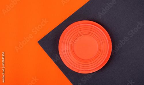 Fotografia Orange clay target on black and orange geometric background