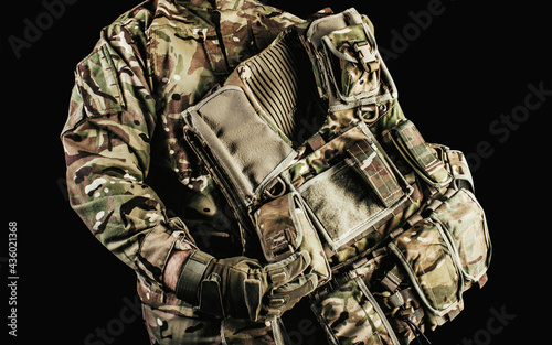 Photo of soldier holding level 3 camouflaged armored vest with shoulder and neck protection on black background Fototapet