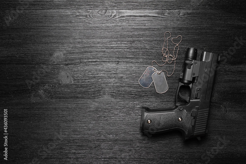Obraz na płótnie Black airsoft gun and soldier badge on the black flat lay background with copy space