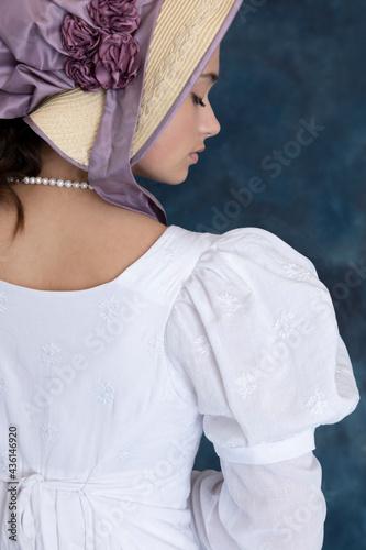 A young Regency woman wearing a white muslin dress and a straw bonnet Fototapet