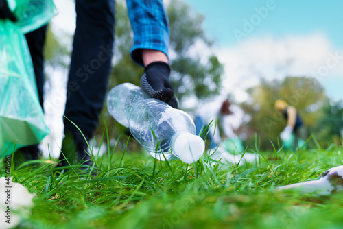 Obraz na plátně Hand of man picking up bottle into garbage bags while cleaning area in park