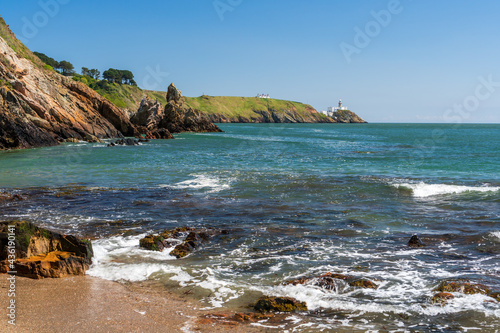 Obraz na plátne Beach, rocks and waves with Baily Lighthouse in the distance