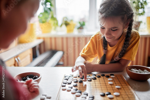 Obraz na plátně Brother and sister playing Chinese chess go at home, sibling have fun together w