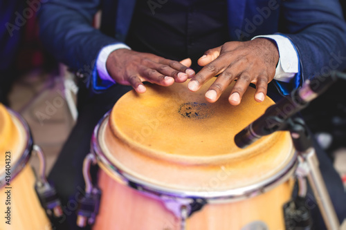 Fotografie, Obraz Bongo drummer percussionist performing on a stage with conga drums set kit durin