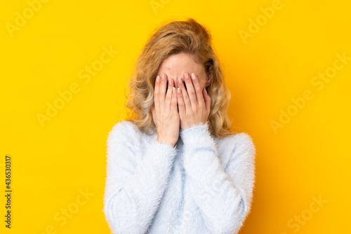 Canvas-taulu Young blonde woman isolated on yellow background with tired and sick expression