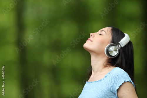 Fotografija Asian woman breathing listening music with headphones